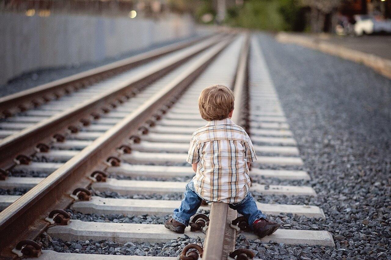 Мальчик сидит на ЖД путях
