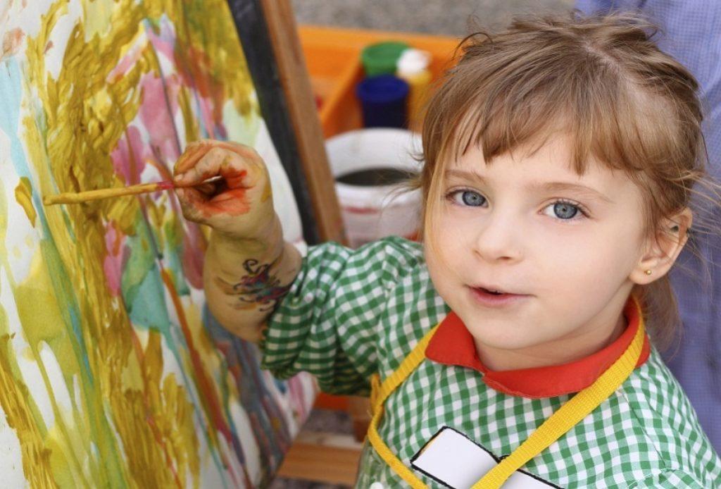 Девочка рисует красками в ДОУ