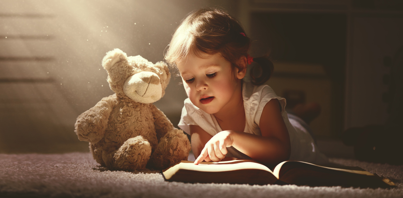 Девочка читает книгу игрушечному медведю