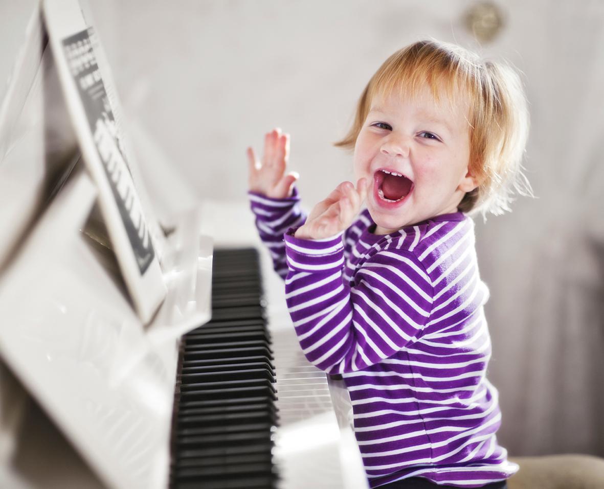 Малыш радуется, играет на писанино