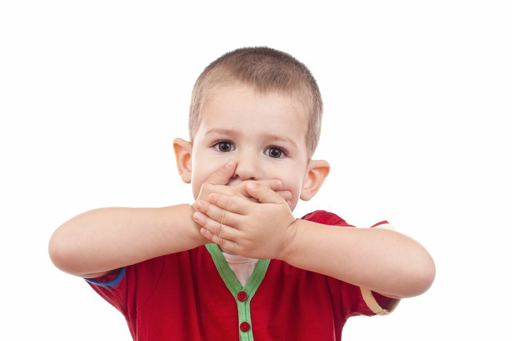 Заикающийся мальчик закрыл руками рот