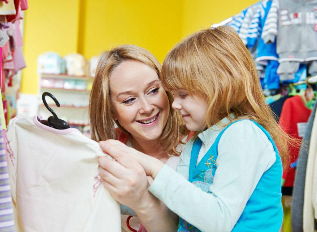 Мама показывает дочке новую кофту в магазине