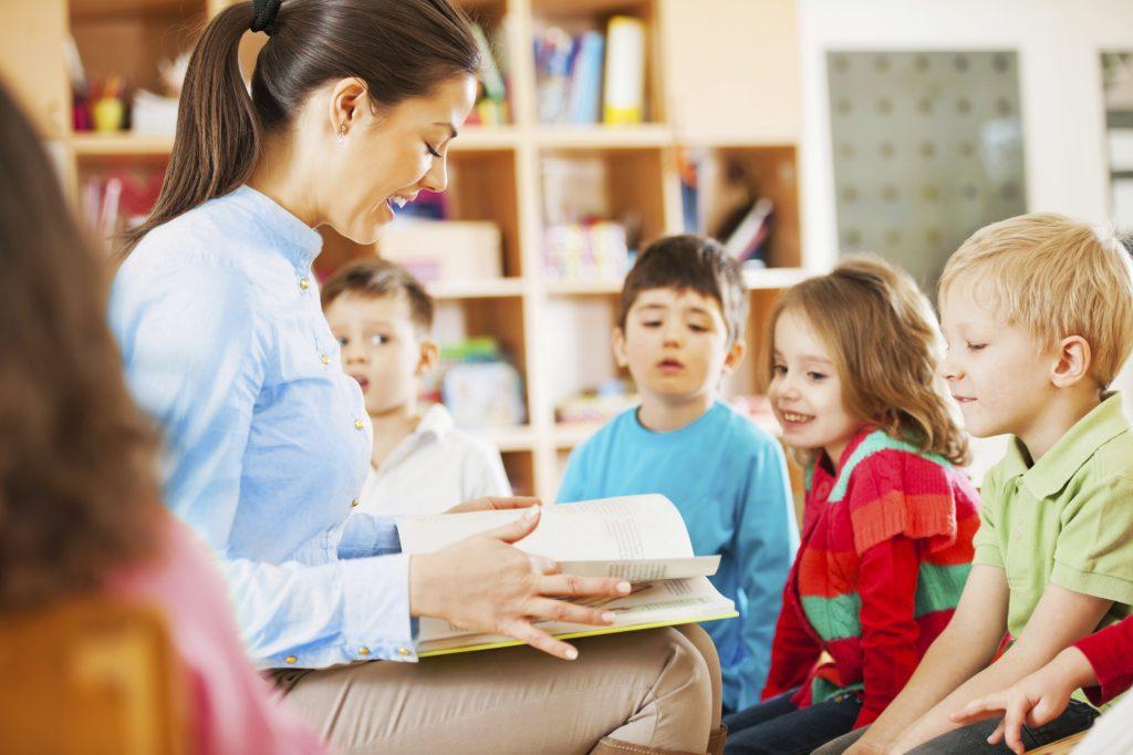 Педагог ДОУ читает книгу малышам
