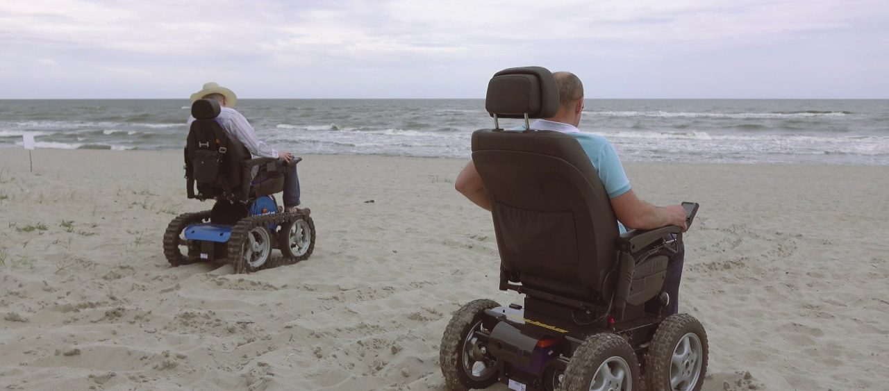 Люди на инвалидных колясках едут по пляжу