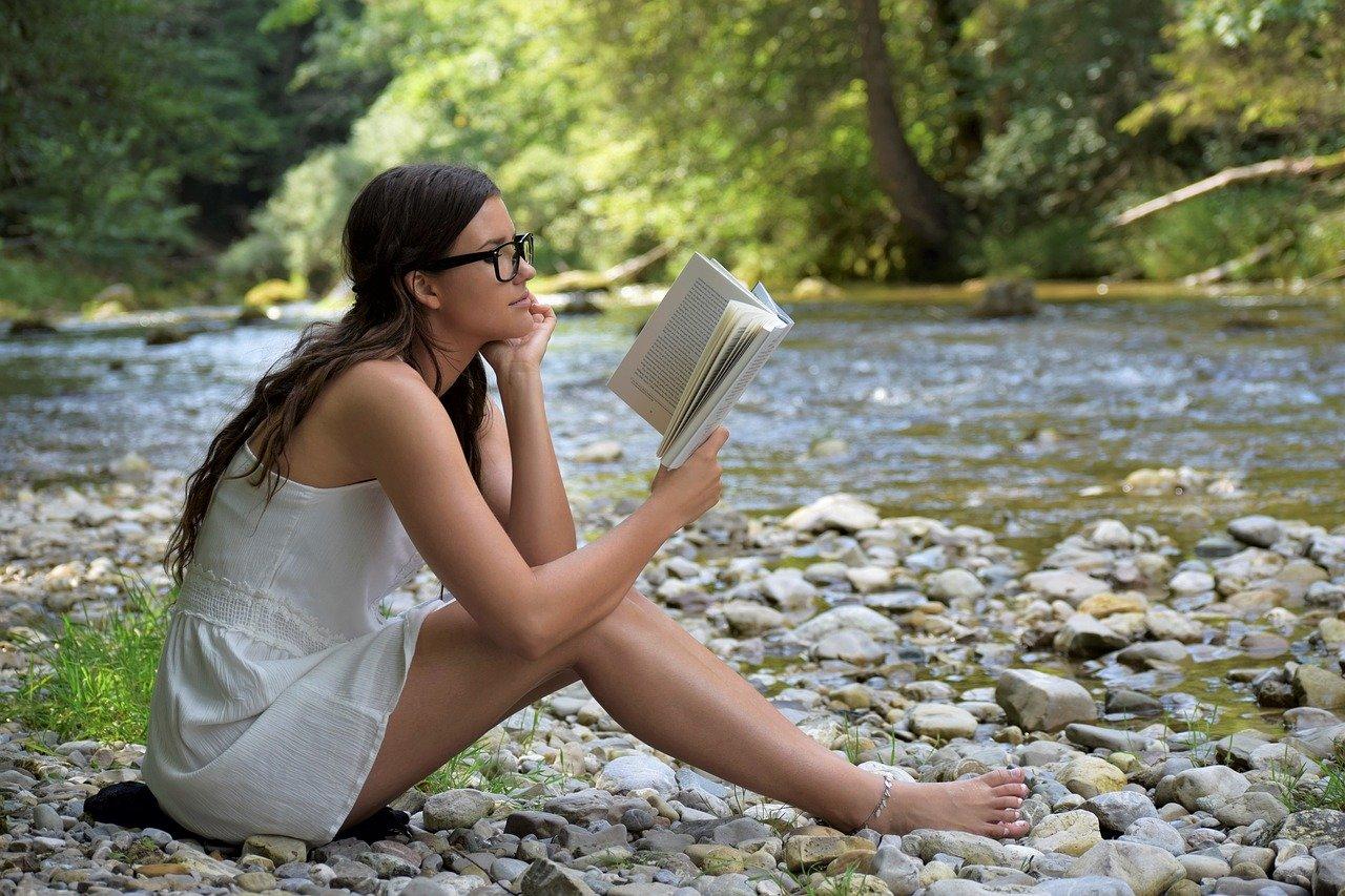 Девушка читает книгу на берегу реки