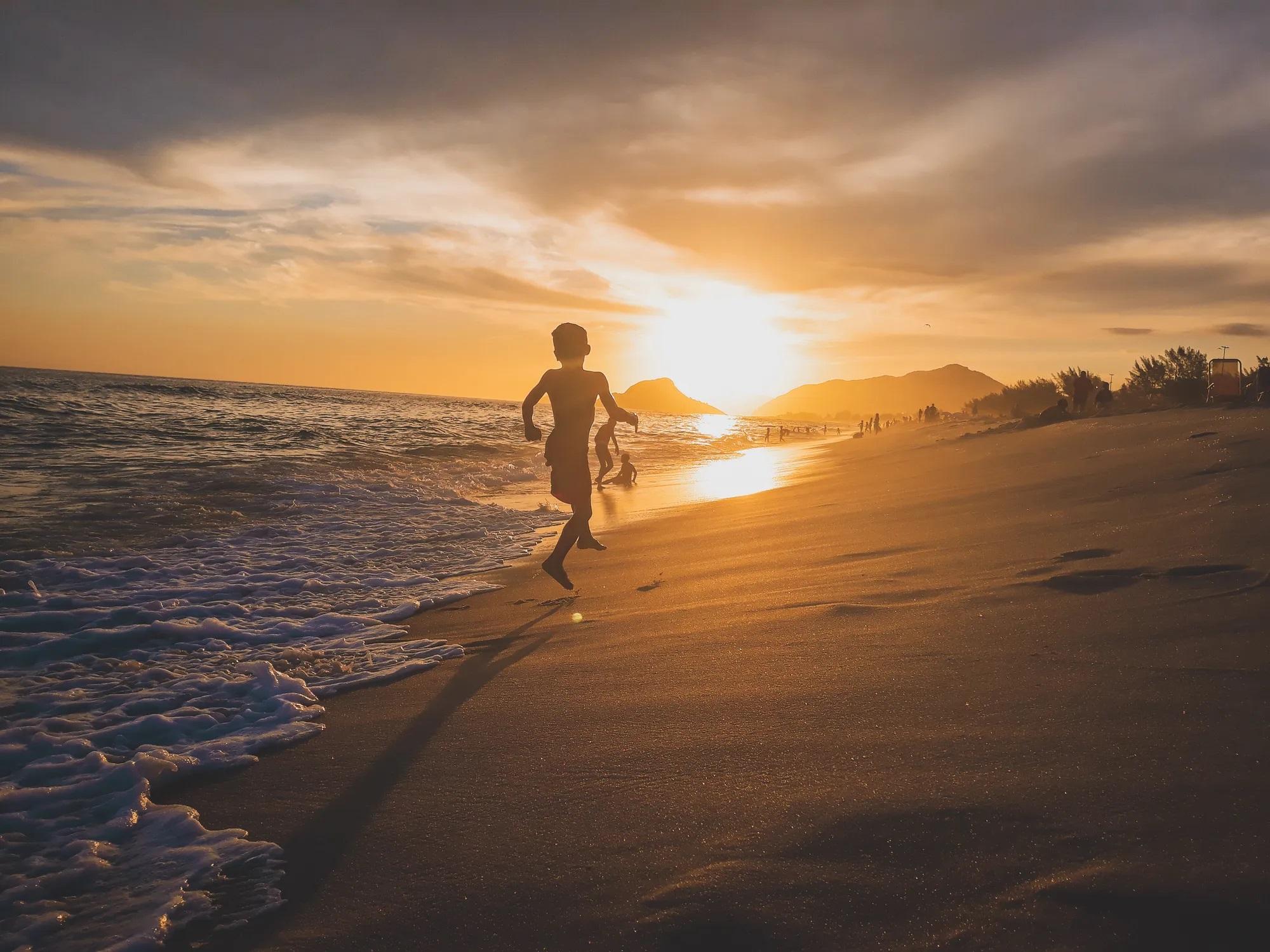 Дети бегают по пляжу вечером