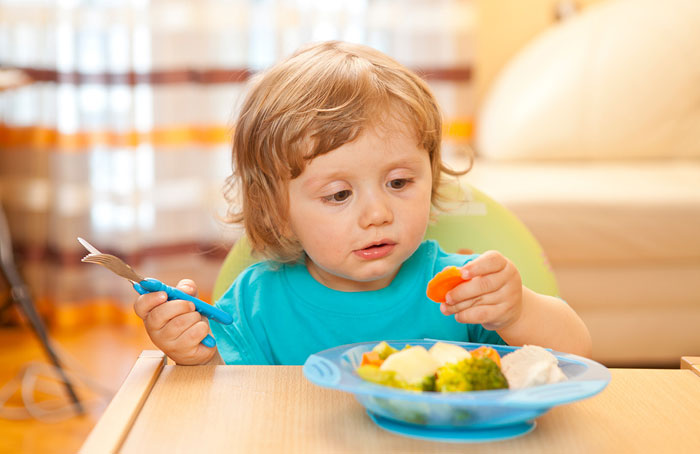 Мальчик рассматривает овощи из тарелки