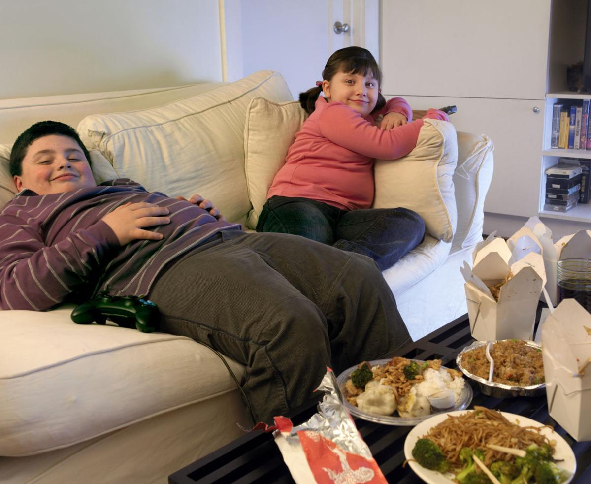 Толстые дети едят и смотрят мультики
